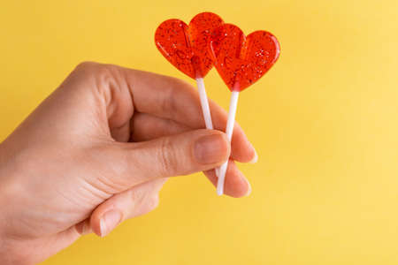 Two sweet bright red lollipops in woman's hand on bright yellow background. Copy space. Stock fotó