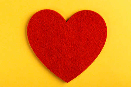 Red felt heart on bright yellow background. St. Valentine's day. Copy space