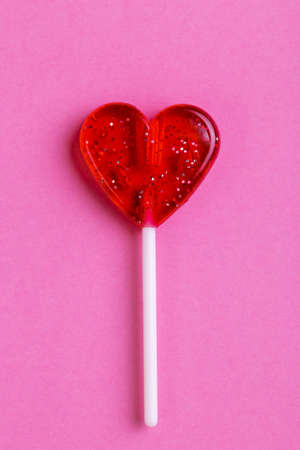 Red sweet tasty lollipop in shape of heart on bright pink background. St. Valentine's day. Copy space