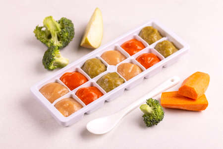 Multicolored pureed baby food in ice cube trays ready for freezing with ingredients on clean white background. Copy space Imagens - 111506854
