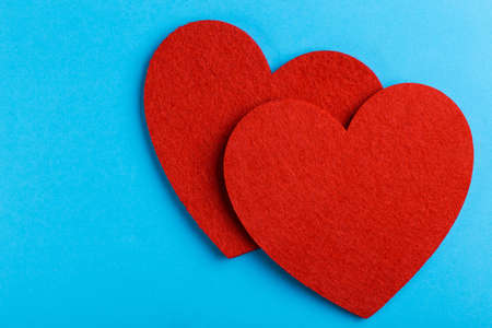 Two red felt heart on bright blue background. St. Valentine's day. Copy space