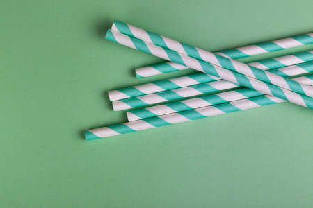 Colorful paper straws on bright green background. Event and party supplies. Earth pollution concept. Copy space