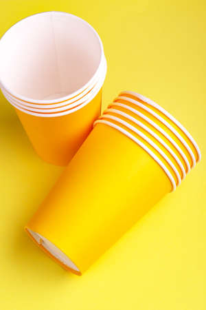 Recycling paper cups for drinks on bright yellow background. Copy space. Party and recycling concept