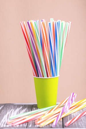 Colorful plastic straws in paper cup on wooden background. Event and party supplies. Earth pollution concept Imagens