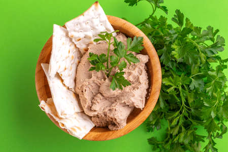 Fresh homemade chicken liver pate with matzo and parsley in wooden bowl on bright green background