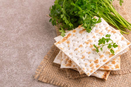 Traditional Jewish kosher matzo with bunch of fresh parsley on rustic burlap napkin. Copy space Stock Photo