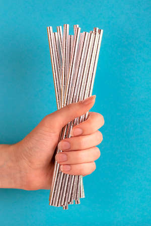 Woman is holding siver paper straws in hand on bright background. Event and party supplies. Earth pollution concept. Copy space
