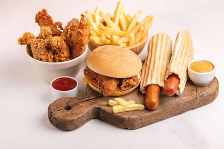 Delicious but unhealthy food with ketchup and mustard on vintage cutting board. Fast carbohydrates, junk and fast food. Light marble background. Banco de Imagens