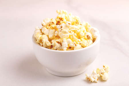 Tasty salty popcorn in bowl on light marble backgraund. Pastime watching movies. Cinema snacks. Copy space Archivio Fotografico