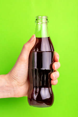 Bottle of black fizzy soda in woman's hand on bright colorful background. Beverage industry. Unhealthy drink. Copy space