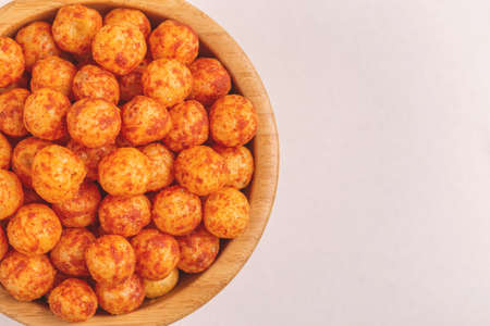 Full wooden bowl of bacon corn puff balls on light background. Cinema snacks. Copy space