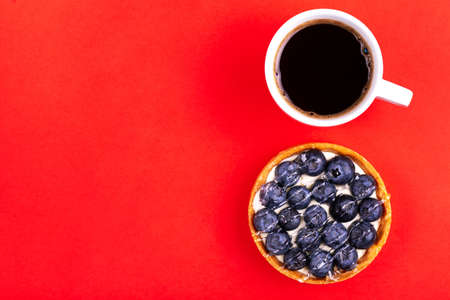 Delicious blueberry tartlet with vanilla cream and fresh cup of coffee on bright red background. Copy space. Top view