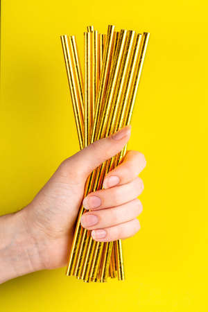 Woman is holding golden paper straws in hand on bright background. Event and party supplies. Earth pollution concept. Copy space