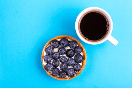 Delicious blueberry tartlet with vanilla cream and fresh cup of coffee on bright blue background. Copy space. Top view