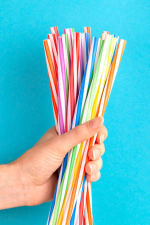 Woman is holding colorful plastic straws in hand on bright background. Event and party supplies. Earth pollution concept Imagens