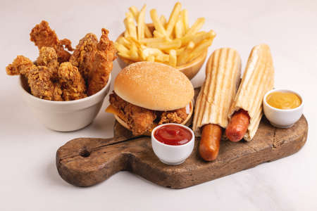 Delicious but unhealthy food with ketchup and mustard on vintage cutting board. Fast carbohydrates, junk and fast food. Light marble background. Imagens