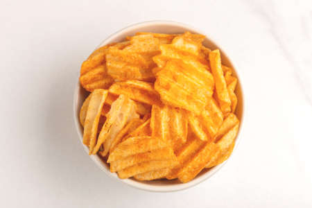 Crunchy corrugated potato chips in white bowl on light marble background. Junk food. Copy space