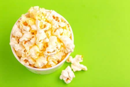 Tasty salty popcorn in paper cup on bright green backgraund. Pastime watching movies. Cinema snacks. Copy space Stock Photo