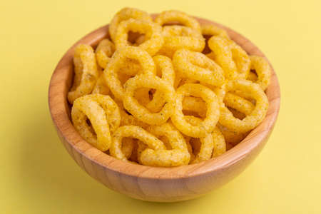 Puff corn rings in wooden bowl on bright colored background. Snacks for watching movies. Copy space Standard-Bild