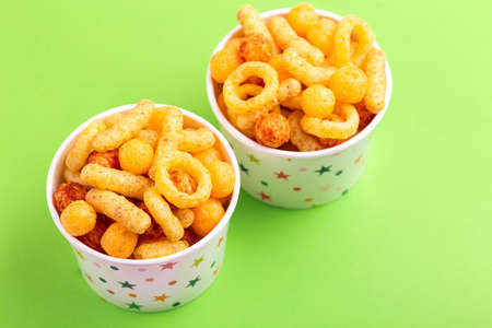 Assorted puff corn snacks in two paper cup on bright colored background. Snacks for watching movies. Copy space