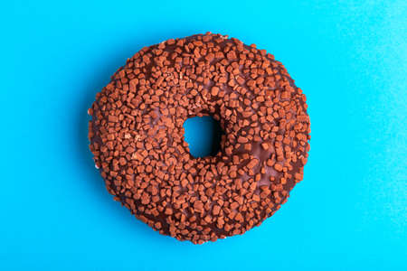 Tasty chocolate donut on bright blue background. Unhealthy, but delicious sweets. Copy space. Top view Imagens