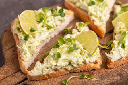 Toasts with avocado pate, fresh microgreen and lime on vintage cutting board. Dark concrete background. Healthy and tasty breakfast Stock Photo