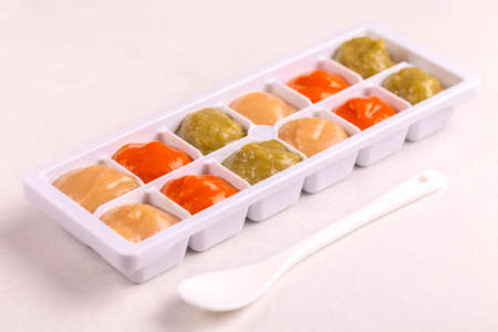 Multicolored pureed baby food in ice cube trays ready for freezing with ispoon on clean white background. Copy space