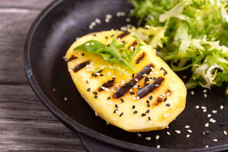 Vegetarian salad with grilled mango, fresh frisee and sesame seeds in cast-iron pan. Dark wooden background. Healthy food concept.
