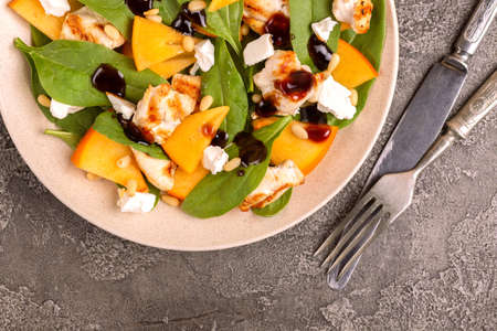 Exotic salad with spinach, persimmon, grilled chicken fillet, feta and pine nuts served in plate with knife and fork. Dark concrete background. Copy space. Top view