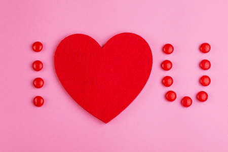 Love confession with help of glazed red chocolate candies and felt heart on pink background. Valentine's day. Flat lay
