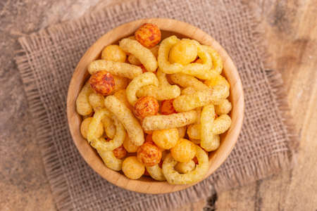 Mixed puff corn snacks in wooden bowl on burlap napkin. Cinema snacks. Copy space