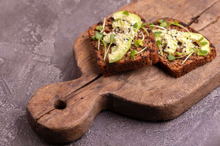 Healthy rye toasts with avocado, radish sprouts and sesame on burlap napkin. Wooden background. Simple breakfast.