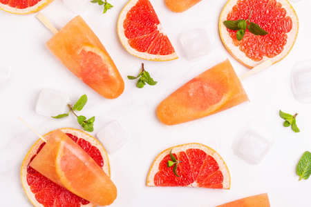 Homemade grapefruit ice pop with ripe grapefruit slices and fresh mint on light marble background. Healthy desserts. Lactose free ice cream. Reklamní fotografie - 114929295