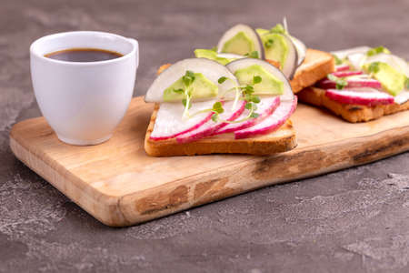 Tasty wheat toasts with radish, avocado and sprouts, cup of strong coffee on wooden cutting board. Dark concrete background. Simple healthy breakfast. Copy space. 免版税图像