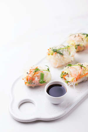Fresh assorted Vietnamese spring rolls with shrimps and vegetables on white background. Copyspace