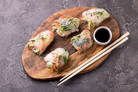 Fresh assorted Vietnamese spring rolls with shrimps and vegetables on dark background. Copyspace