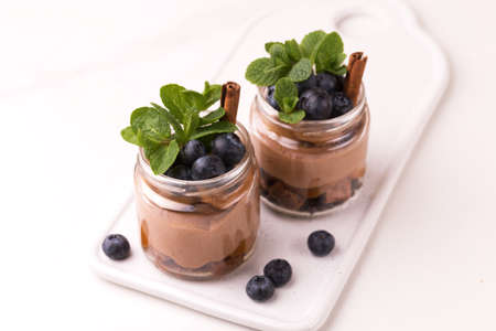 Homemade cake dessert. Chocolate mousse with blueberry, mint and cinnamon in glass jars.