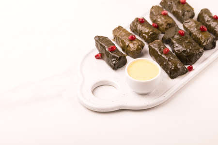 Traditional georgian cuisine. Dolma in grape leaves with pomegranate and parsley Imagens