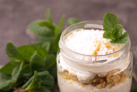 Layered coconut bisquit dessert with ricotta, mint and honey in glass jar. Yogurt breakfast Imagens