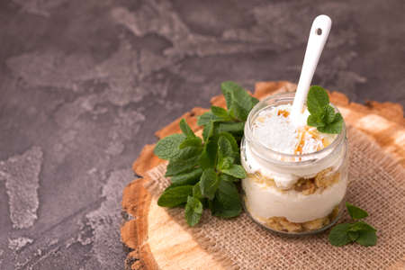 Layered coconut bisquit dessert with ricotta, mint and honey in glass jar. Yogurt breakfast Banque d'images