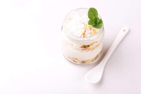 Layered coconut bisquit dessert with ricotta, mint and honey in glass jar. Yogurt breakfast Imagens - 122262936