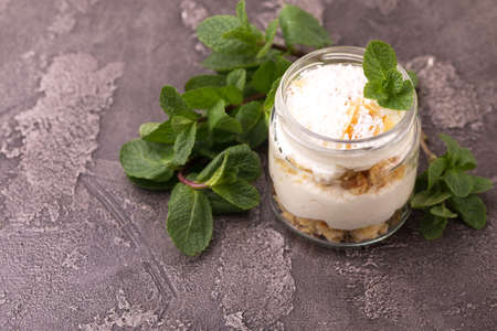 Layered coconut bisquit dessert with ricotta, mint and honey in glass jar. Yogurt breakfast Imagens - 122526590