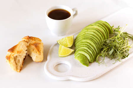 Healthy breakfast with avocado, bun, pea sprouts, lime, pesto and coffee. White background. Vegetarian, diet