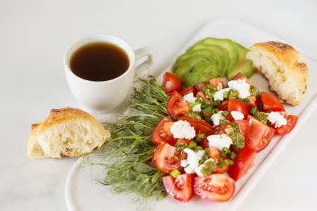 Healthy breakfast salad with tomatoes, avocado, bun, pea sprouts, ricotta, pesto and coffee. White background. Vegetarian, diet