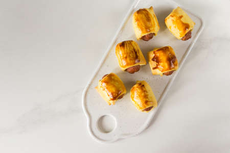 Pastry wrapped sausage rolls, fried sausage pies in dough. Junk food concept Standard-Bild - 129610717