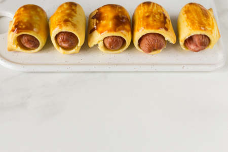 Pastry wrapped sausage rolls, fried sausage pies in dough. Junk food concept Standard-Bild - 129610724