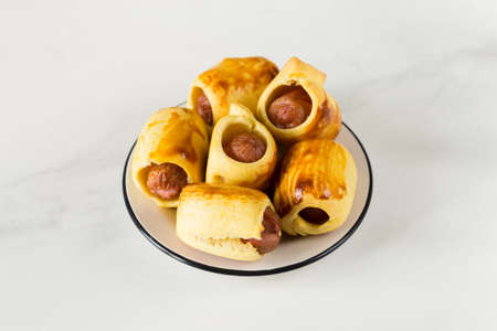 Pastry wrapped sausage rolls, fried sausage pies in dough. Junk food concept Standard-Bild - 129610865