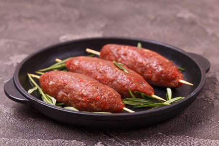 raw lula kebab, lyulya-kebab minced meat, shish kebab ready to cook with rosemary. Caucasian cuisine. Fast food. Eastern food.