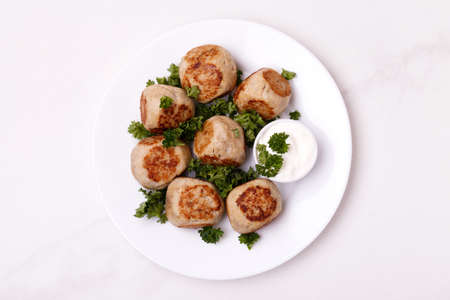 Homemade swedish meatballs with sour cream sauce and parsley