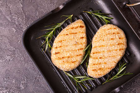 Grilled Chicken or Turkey Breast with rosemary on black background, top view